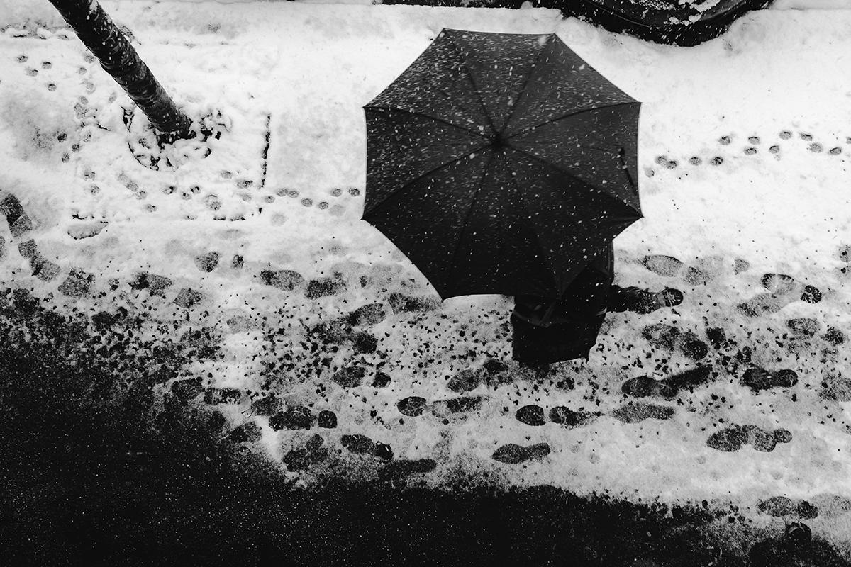 Un uomo con ombrello ripreso dall'alto su manto di neve
