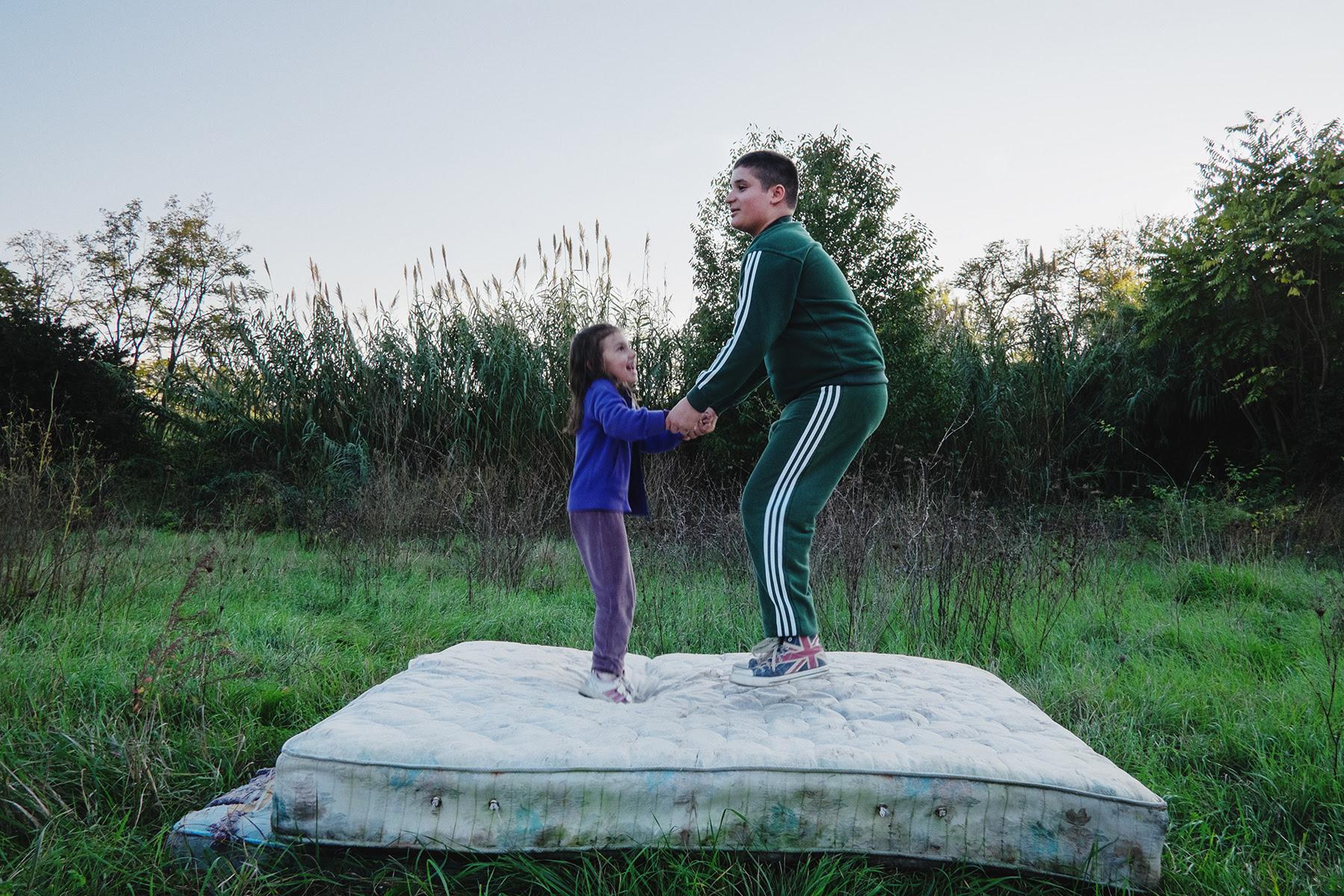 bambini che saltano su materasso in campo